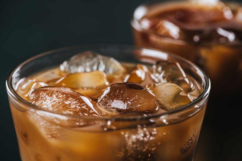 Nahaufnahme von Eiswürfeln in kalt gebrühtem Kaffee im Glas auf dunklem Hintergrund.