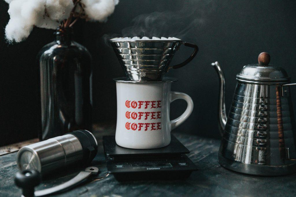 Eine Tasse mit Aufschrift, Kaffee und einem Kaffeefilter obendrauf auf einer Waage.