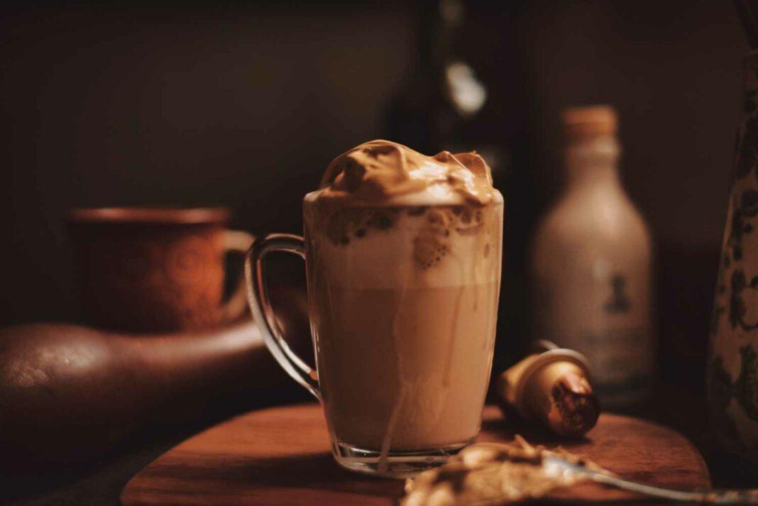 Eine Glas Dalgona-Kaffee vor gemütlichem Hintergrund.